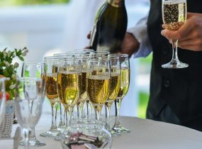 Waiter with champagne on the table, drink in hand