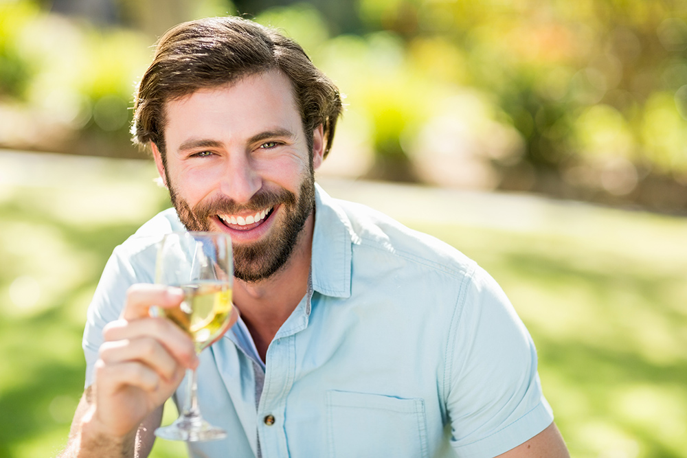 Portrait of man holding wine glass and smiling in park