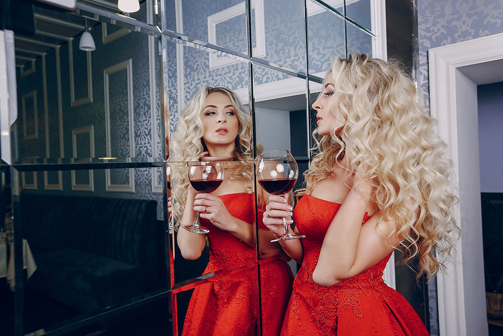 elegant and beautiful lady in red dress in a restaurant with a glass of expensive wine