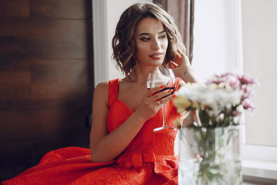 elegant and beautiful lady in red dress sitting in a restaurant with a glass of expensive wine
