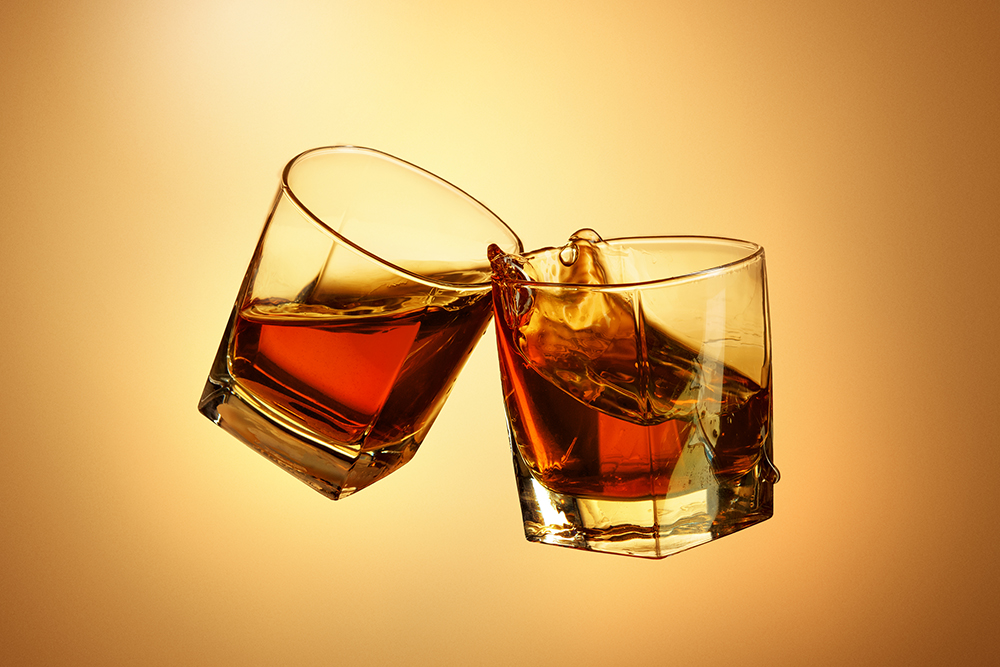 Two whiskey glasses clinking together on brown studio background