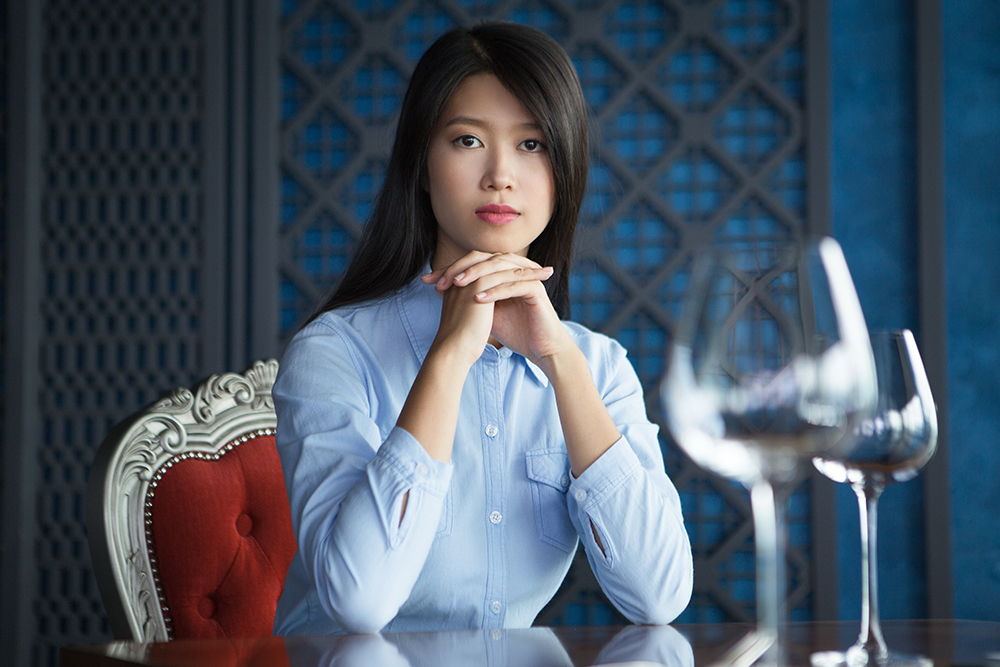 Portrait of pretty young Asian woman with her hands under chin sitting at table in luxury restaurant, looking at camera